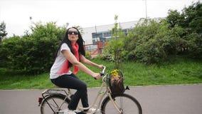 Πορτρέτο της ευτυχούς νέας γυναίκας στο ποδήλατο Στο ποδήλατό της το καλάθι είναι λουλούδια και μια τσάντα Απολαμβάνει το ταξίδι απόθεμα βίντεο