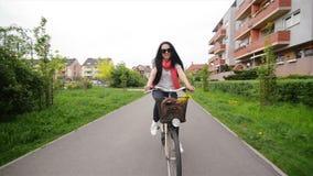 Πορτρέτο της ευτυχούς νέας γυναίκας στο ποδήλατο Στο ποδήλατό της το καλάθι είναι λουλούδια και μια τσάντα Απολαμβάνει το ταξίδι φιλμ μικρού μήκους
