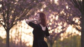 Πορτρέτο της ευτυχούς νέας γυναίκας χορευτών ταξιδιού που απολαμβάνει το ελεύθερο χρόνο σε ένα πάρκο ανθών κερασιών sakura - καυκ απόθεμα βίντεο