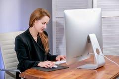 Πορτρέτο της ευτυχούς νέας επιτυχούς επιχειρηματία στο γραφείο Κάθεται στον πίνακα και δακτυλογραφεί στο πληκτρολόγιο, εργασία γρ στοκ εικόνες
