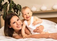 Πορτρέτο της ευτυχούς νέας μητέρας με το γοητευτικό αγοράκι της Στοκ Εικόνες