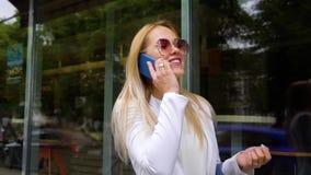 Πορτρέτο της ευτυχούς ξανθής παντρεμένης ομιλίας γυναικών στο smartphone της στην οδό απόθεμα βίντεο