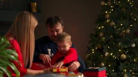 Πορτρέτο της ευτυχούς οικογένειας που ανοίγει ένα κιβώτιο δώρων χριστουγεννιάτικου δώρου το βράδυ Έννοια των διακοπών, έκπληξη, ε απόθεμα βίντεο