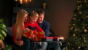 Πορτρέτο της ευτυχούς οικογένειας που ανοίγει ένα κιβώτιο δώρων χριστουγεννιάτικου δώρου το βράδυ Έννοια των διακοπών, έκπληξη, ε φιλμ μικρού μήκους