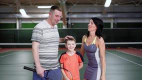 Πορτρέτο της ευτυχούς οικογένειας στην αθλητική εξάρτηση που στέκεται με τις ρακέτες στην περιοχή αναψυχής που αγκαλιάζει και που φιλμ μικρού μήκους