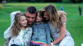 Πορτρέτο της ευτυχούς οικογένειας στο πάρκο φιλμ μικρού μήκους