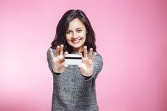 Πορτρέτο της ευτυχούς πιστωτικής κάρτας εκμετάλλευσης νέων κοριτσιών πέρα από το ρόδινο υπόβαθρο στοκ εικόνες