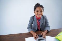 Πορτρέτο της ευτυχούς προσποίησης κοριτσιών ως επιχειρηματία που χρησιμοποιεί τον υπολογιστή Στοκ Φωτογραφίες