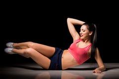 Πορτρέτο της ευτυχούς φίλαθλης γυναίκας που κάνει την άσκηση ABS Χαρούμενο θηλυκό πρότυπο που εκπαιδεύει στο εσωτερικό Υγιής ενερ Στοκ Φωτογραφίες
