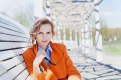 Πορτρέτο της ευτυχούς χαμογελώντας επιχειρησιακής γυναίκας ή του σπουδαστή μόδας με τα γυαλιά ηλίου που κάθεται στον πάγκο υπαίθρ Στοκ Φωτογραφίες