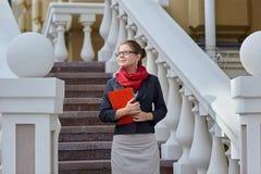 Πορτρέτο της ευτυχούς χαμογελώντας επιχειρησιακής γυναίκας στα γυαλιά με τον κόκκινο φάκελλο Στοκ Εικόνα