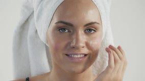 Πορτρέτο της ευτυχούς χαμογελώντας όμορφης νέας γυναίκας σχετικά με το δέρμα ή την εφαρμογή της κρέμας, μετά από το ντους με την  φιλμ μικρού μήκους
