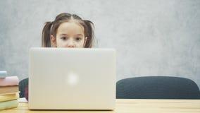 Πορτρέτο της ευτυχούς χαριτωμένης έξυπνης συνεδρίασης κοριτσιών με το σωρό των βιβλίων και του lap-top στον πίνακα, διάστημα αντι φιλμ μικρού μήκους