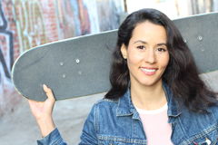 Πορτρέτο της ευτυχούς όμορφης γυναίκας με τη μακριά προκλητική υγιή τρίχα στο σακάκι τζιν με skateboard της που εξετάζει τη κάμερ στοκ εικόνα με δικαίωμα ελεύθερης χρήσης