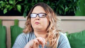 Πορτρέτο της ευχάριστης παχιάς γυναίκας που τρώει τα ανθυγειινά τσιπ που έχουν τη θετική συγκίνηση που εξετάζει τη κάμερα απόθεμα βίντεο