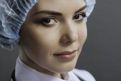 Πορτρέτο της ευχαριστημένης θηλυκής τοποθέτησης γιατρών στο γκρίζο υπόβαθρο στοκ εικόνες