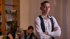 Πορτρέτο της εφηβικής αραβικής προσοχής αγοριών άμεσα στη κάμερα με τα όπλα που διασχίζονται και την οικογένειά του στο υπόβαθρο φιλμ μικρού μήκους