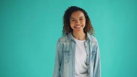 Πορτρέτο της εύθυμης γυναίκας αφροαμερικάνων που γυρίζει στη κάμερα και το γέλιο φιλμ μικρού μήκους