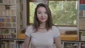 Πορτρέτο της εύθυμης νέας γυναίκας που χαμογελά και που παρουσιάζει αντίχειρες - φιλμ μικρού μήκους