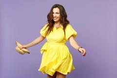 Πορτρέτο της εύθυμης χαμογελώντας νέας γυναίκας στο κίτρινο θερινό καπέλο εκμετάλλευσης φορεμάτων, που φαίνεται κάμερα στη βιολέτ στοκ εικόνα