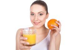 Πορτρέτο της ελκυστικής καυκάσιας χαμογελώντας γυναίκας που πίνει το πορτοκαλί j Στοκ Εικόνα