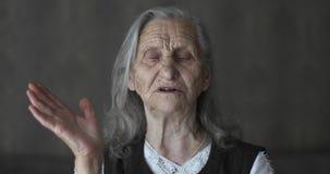 Πορτρέτο της ηλικιωμένης γυναίκας με την γκρίζα ιστορία αφήγησης τρίχας και τα gesticulating χέρια φιλμ μικρού μήκους