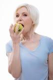 Πορτρέτο της ηλικιωμένης γυναίκας δαγκώνοντας το πράσινο μήλο στοκ εικόνες με δικαίωμα ελεύθερης χρήσης
