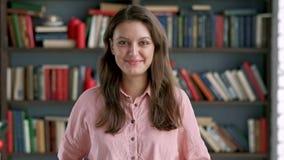 Πορτρέτο της καλής νέας στάσης γυναικών βιβλιοθηκάριων στο ελκυστικό χαμόγελο σπουδαστών βιβλιοθηκών κοντά επάνω απόθεμα βίντεο