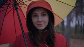 Πορτρέτο της καυκάσιας γυναίκας στην κουκούλα και κάτω από την ομπρέλα το φθινόπωρο στην οδό απόθεμα βίντεο