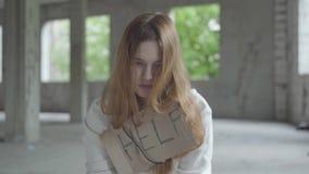 Πορτρέτο της καυκάσιας νέας λυπημένης συνεδρίασης κοριτσιών σε ένα εγκαταλειμμένο κτήριο που έχει το φάρμακο που σπάζει ή που περ φιλμ μικρού μήκους