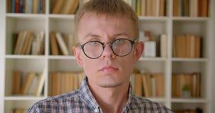 Πορτρέτο της καυκάσιας προσοχής βιβλιοθηκάριων με προσήλωση και σοβαρά στη κάμερα που καθορίζει eyeglasses του στα ράφια απόθεμα βίντεο