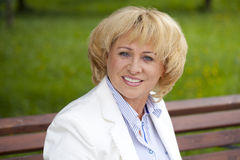 Πορτρέτο της καλής μέσης ηλικίας γυναίκας στο θερινό πάρκο στοκ φωτογραφία
