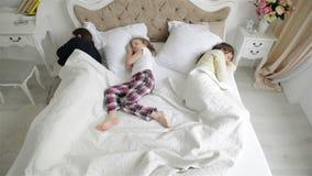 Πορτρέτο της κοιμισμένης οικογένειας το πρωί στην κρεβατοκάμαρα Χαριτωμένη λίγη κόρη κοιμάται μεταξύ των γονέων Σύζυγος και απόθεμα βίντεο
