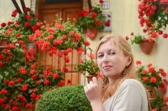 Πορτρέτο της κοκκινομάλλους γυναίκας μπροστά από τα κόκκινα λουλούδια Στοκ εικόνα με δικαίωμα ελεύθερης χρήσης