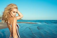 Πορτρέτο της κομψής ξανθής γυναίκας στο ριγωτό φόρεμα με τη γυμνή πίσω στάση στην παραλία και να φανεί ευθύς στοκ εικόνες