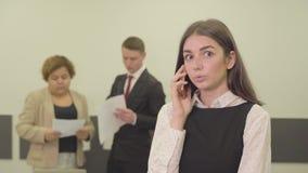 Πορτρέτο της λατρευτής ελκυστικής νέας γυναίκας στην επίσημη ένδυση που μιλά από το κινητό τηλέφωνο στο πρώτο πλάνο στο γραφείο ε φιλμ μικρού μήκους