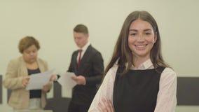 Πορτρέτο της λατρευτής νέας γυναίκας στην επίσημη ένδυση που κοιτάζει στη κάμερα στο πρώτο πλάνο στο γραφείο ενώ το αρσενικό της  απόθεμα βίντεο