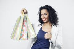 Πορτρέτο της μαύρης γυναίκας ευχαριστημένο από τις τέλειες τσάντες εγγράφου αγορών, πρόσωπο χαμόγελου Στοκ Φωτογραφίες