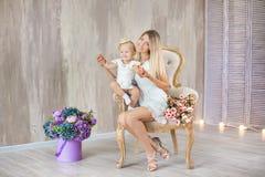 Πορτρέτο της μητέρας και της κόρης καλών αγκαλιάζοντας ο ένας τον άλλον που θέτει στην αναδρομική καρέκλα με την ανθοδέσμη των λο στοκ εικόνες