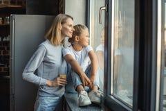 πορτρέτο της μητέρας και της κόρης που φαίνονται έξω παράθυρο από κοινού Στοκ Εικόνες