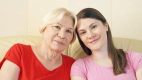 Πορτρέτο της μητέρας και της νέας χαλάρωσης κορών στον καναπέ στο σπίτι Ευτυχής οικογένεια που απολαμβάνει το χρόνο από κοινού απόθεμα βίντεο