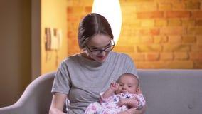 Πορτρέτο της μητέρας που μιλά με τη χαριτωμένη νεογέννητη κόρη της στο καθιστικό απόθεμα βίντεο