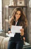 Πορτρέτο της μοντέρνης νέας γυναίκας με τις καφετιές τρίχες που διαβάζει την επιστολή Στοκ φωτογραφία με δικαίωμα ελεύθερης χρήσης