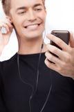 Πορτρέτο της μουσικής ακούσματος νεαρών άνδρων στο τηλέφωνο κυττάρων Στοκ εικόνες με δικαίωμα ελεύθερης χρήσης