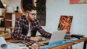 Πορτρέτο της νέας γραφικής εργασίας σχεδιαστών για το lap-top στο εσωτερικό στοκ εικόνες