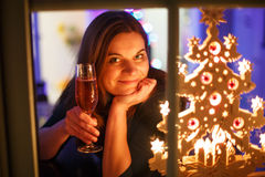Πορτρέτο της νέας γυναίκας μέσω του παραθύρου που γιορτάζει τη Ev του νέου έτους Στοκ φωτογραφία με δικαίωμα ελεύθερης χρήσης