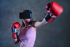 Πορτρέτο της νέας γυναίκας με τα εγκιβωτίζοντας γάντια που παίζουν το τηλεοπτικό παιχνίδι που χρησιμοποιεί τα προστατευτικά δίοπτ Στοκ Φωτογραφία