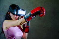 Πορτρέτο της νέας γυναίκας με τα εγκιβωτίζοντας γάντια που παίζουν το τηλεοπτικό παιχνίδι που χρησιμοποιεί τα προστατευτικά δίοπτ Στοκ Εικόνες