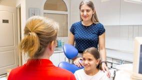 Πορτρέτο της νέας γυναίκας με την κόρη της που μιλά στον παιδιατρικό οδοντίατρο Στοκ εικόνες με δικαίωμα ελεύθερης χρήσης