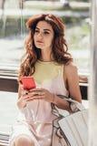 πορτρέτο της νέας γυναίκας με τη συνεδρίαση smartphone στοκ φωτογραφίες